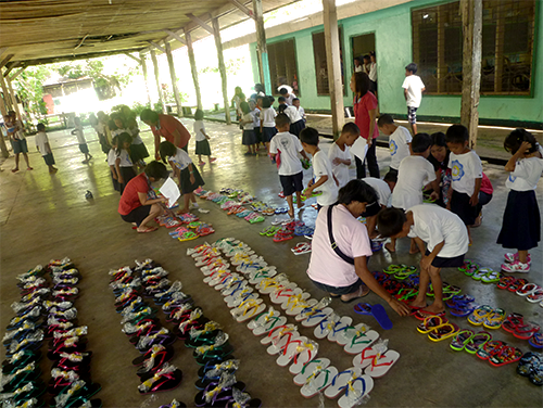 Photo of pupils or students trying on new footwear or flip flops at Binanuahan Elementary School, Pilar, Sorsogon, Philippines